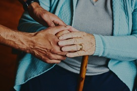 Caregiver holding hands of elderly care home resident