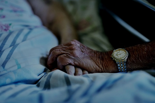 Man holding elderly deceased lady in a care home bed