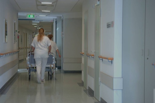 Nurses pulling a hospital maternity bed