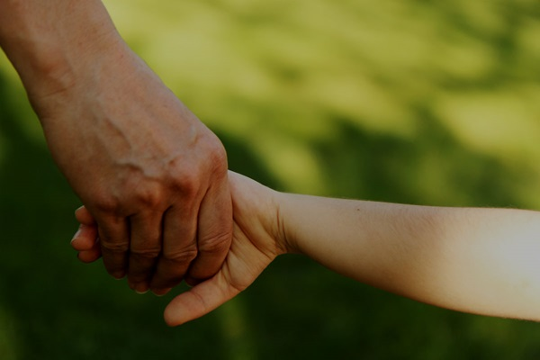 adult safeguarding child holding hands