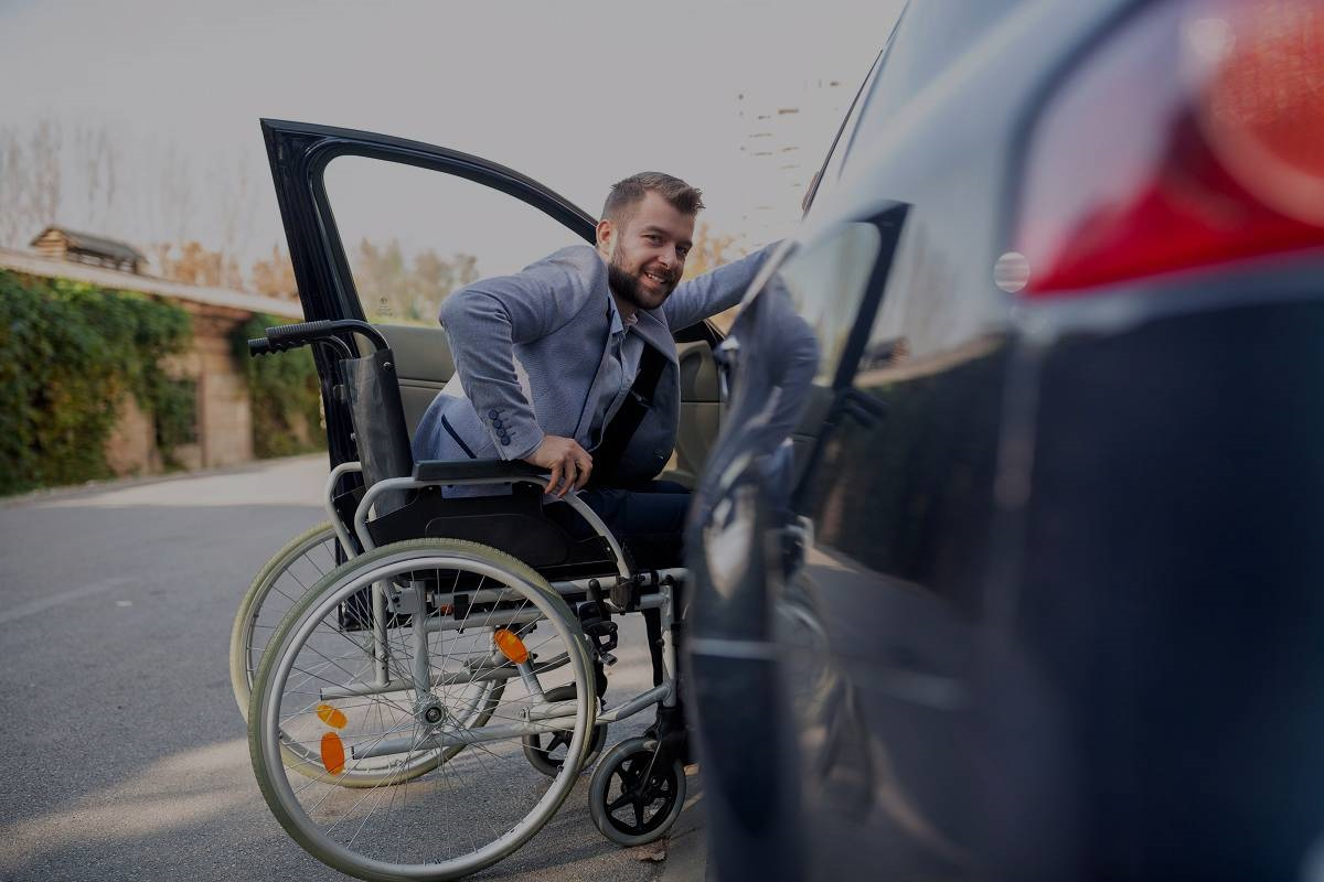 young man with spinal cord injury in a wheelchair trying to get into a car